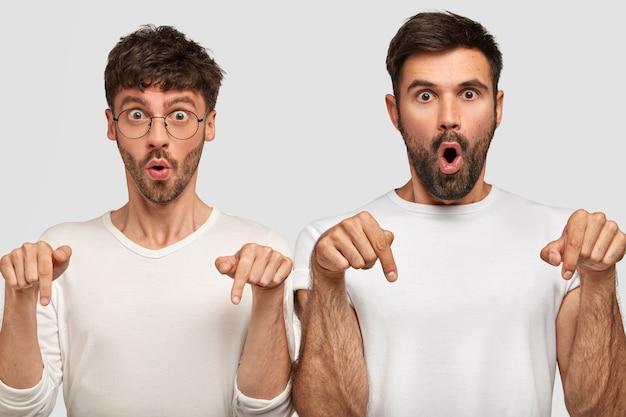 Dois homens surpresos com expressões faciais confusas e assustadas apontam um para o outro, mostram algo no chão, mantêm a boca aberta