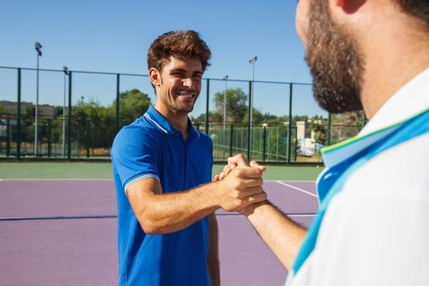 Dois homens, tenistas profissionais apertam as mãos antes e depois da partida de tênis