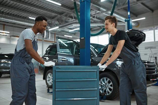 Dois homens trabalhadores na caixa de ferramentas na oficina mecânica.