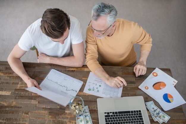 Dois homens trabalhando juntos em um projeto e parecendo concentrados