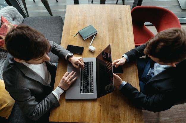 Dois homens trabalhando no laptop durante uma reunião em um café
