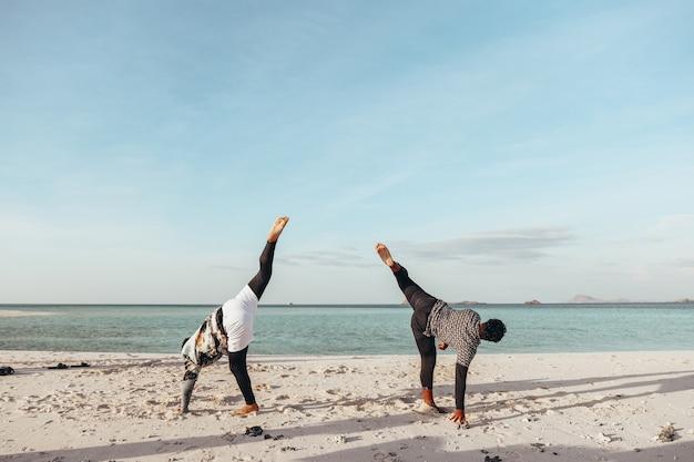 Dois homens treinam arte marcial de capoeira na praia