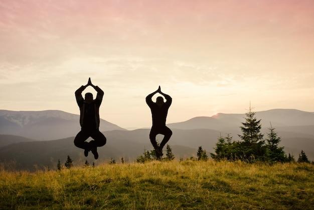 Dois homens voam no ar em posição de ioga na paisagem montanhosa. mediação sobre a natureza