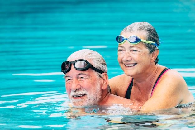Dois idosos abraçados na água da piscina - homem ativo e mulher fazendo exercícios juntos na piscina - abraçados com amor - usando óculos de proteção