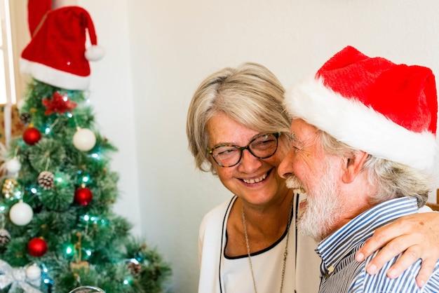 Dois idosos aposentados se divertindo e rindo juntos em casa com uma árvore de natal ao fundo e com o homem maduro usando boné ou boné de natal