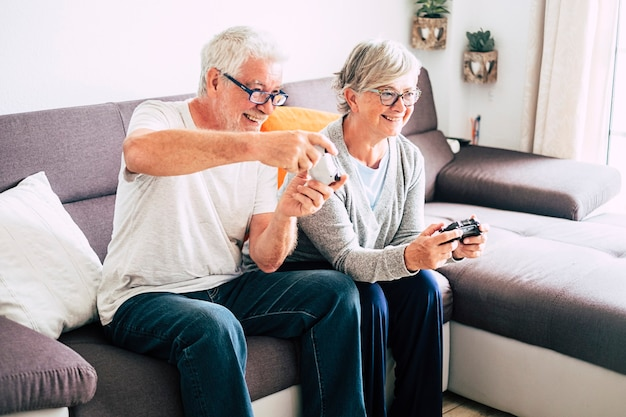 Dois idosos brincando com videogames juntos e se divertindo sentados no sofá em casa - dentro de casa e se divertindo com o estilo de vida