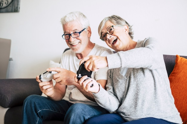 Dois idosos caucasianos aposentados jogando videogame juntos em casa sentados no sofá - mulher madura e homem casado - dois ficam noivos para sempre - segurando um controle ou um joystick