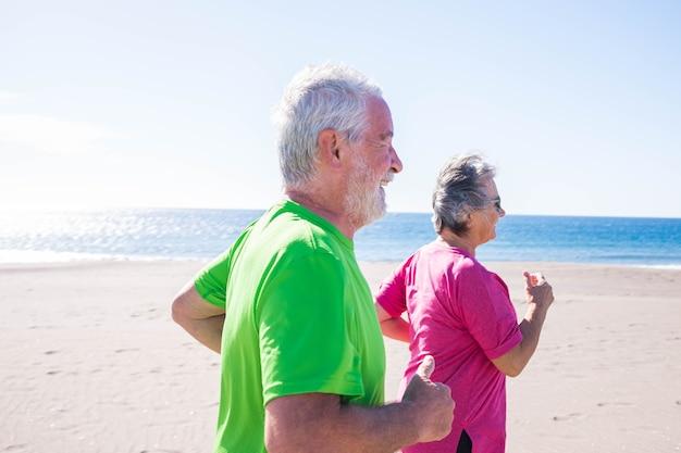 Dois idosos correndo juntos na praia com o mar ao fundo - duas pessoas maduras fazendo jogging e sorrindo