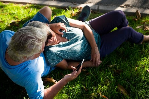Dois idosos deitados na grama do parque abraçados e olhando para o mesmo telefone - aposentados caucasianos felizes e curtindo