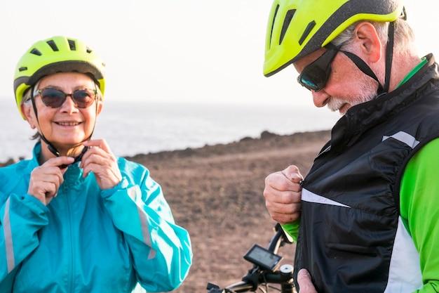 Dois idosos do fitness na montanha fechando seus equipamentos e se preparando para fazer exercícios juntos ou se divertir com suas bicicletas