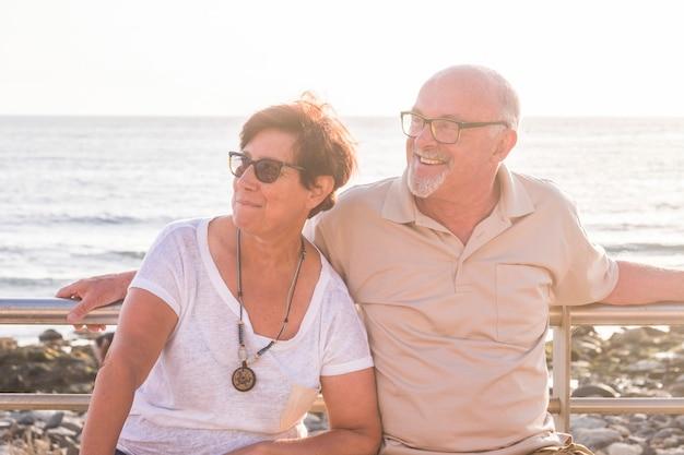 Dois idosos e adultos sentados em um banco na praia com o mar ao fundo olhando para a direita juntos sorrindo e rindo