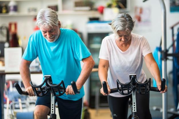 Dois idosos e pessoas maduras no ciclet treinando na academia, pedalando juntos - conceito de estilo de vida de aposentado ativo - homem e mulher sem parar