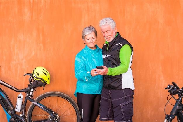 Dois idosos e pessoas maduras se casaram olhando para o mesmo telefone com roupas de ginástica e suas bicicletas - parede laranja ao fundo