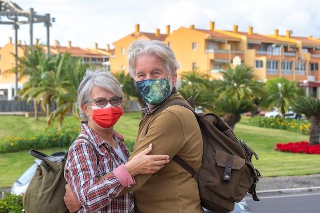 Dois idosos em passeio pela cidade usando máscara cirúrgica devido ao coronavírus
