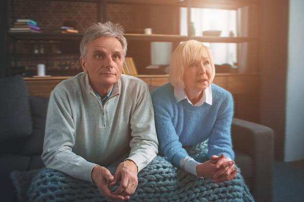 Dois idosos estão sentados juntos.