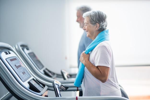 Dois idosos felizes e em forma fazendo exercícios na academia juntos, correndo no tapis roulant - estilo de vida ativo