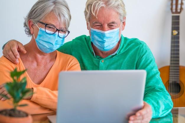 Dois idosos felizes e pessoas maduras conversando com alguém em uma videochamada em casa em um estilo de vida confinado