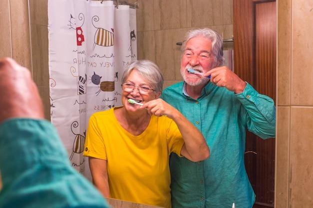 Dois idosos felizes e sorridentes, escovando os dentes um do outro juntos em casa no banheiro - cuidando de si e cuidando de si mesmos