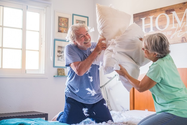 Dois idosos felizes se divertindo brincando juntos na cama em casa brigando com travesseiros desfrutando - guerra de travesseiros dentro de casa pela manhã