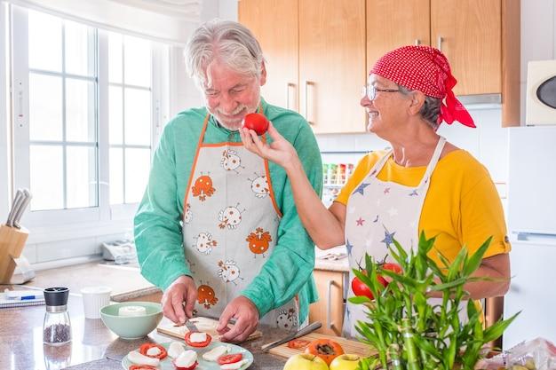 Dois idosos felizes se divertindo e cozinhando juntos na cozinha de sua casa - preparando uma comida saudável com tomates