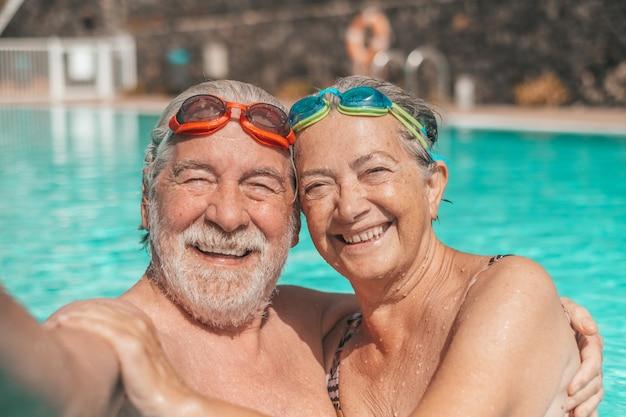 Dois idosos felizes, se divertindo e curtindo juntos na piscina tirando uma foto de selfie, sorrindo e olhando para a câmera. pessoas felizes curtindo o verão ao ar livre na água