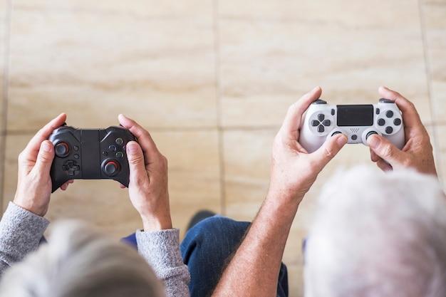 Dois idosos jogando videogame com joystick em casa - dentro de casa, curtindo e se divertindo com jogos - apenas com as mãos