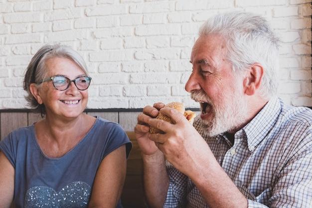 Dois idosos juntos se divertindo comendo e rindo - homem maduro segurando um hambúrguer e comendo com a boca aberta e sua esposa olhando e sorrindo