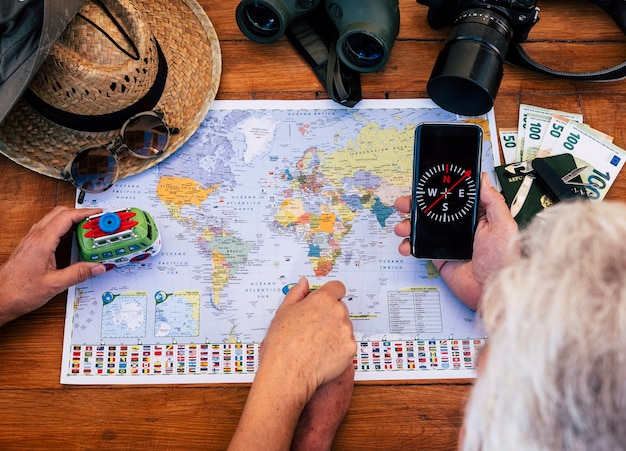 Dois idosos planejando uma viagem de férias em um mapa-múndi verificando o passaporte e os acessórios de viagem - conceito de aventura e liberdade