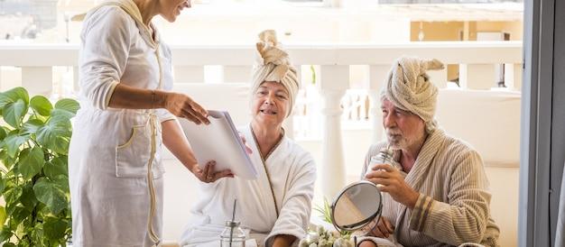 Dois idosos saudáveis e felizes desfrutando de um serviço de massagens e tratamentos com um assistente e se divertindo