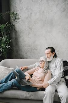 Dois idosos sorrindo e olhando para o mesmo laptop abraçados no sofá
