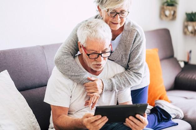 Dois idosos sorrindo e olhando para o mesmo tablet abraçados no sofá - conceito interno, em casa - caucasianos maduros e aposentados e mulheres usando tecnologia