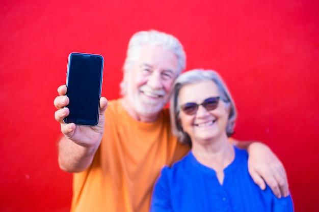 Dois idosos sorrindo e rindo juntos, olhando para a câmera - retrato e close-up de um velho segurando um telefone preto sem na tela