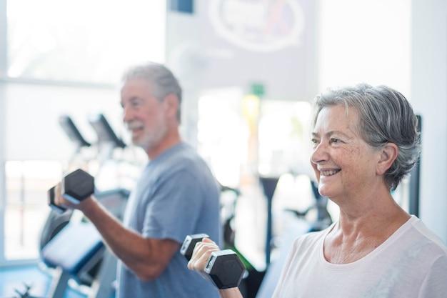 Dois idosos treinando juntos na academia com halteres na mão - conceito de estilo de vida saudável e fitness - treino e levantamento de peso