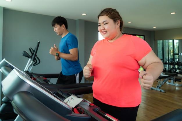 Dois instrutores asiáticos e uma mulher com excesso de peso fazendo exercícios na esteira na academia