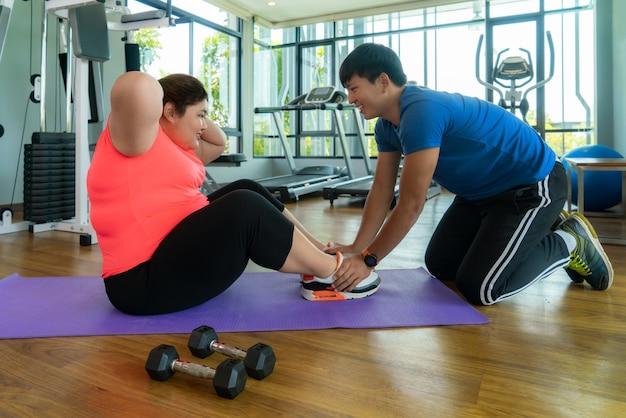 Dois instrutores asiáticos e uma mulher com excesso de peso sentam-se fazendo exercícios juntos em uma academia moderna