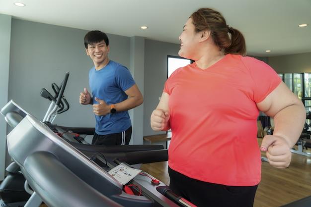 Dois instrutores asiáticos e uma mulher com excesso de peso treinando na esteira na academia