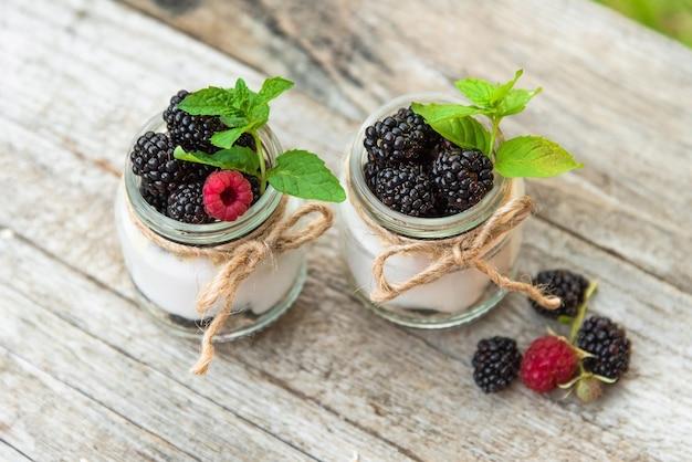 Dois iogurtes frescos com amoras e framboesas na natureza com a adição de folhas de hortelã.