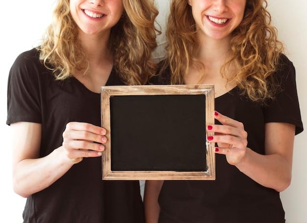 Dois, irmã, mostrando, ardósia branca, isolado, sobre, branca, fundo