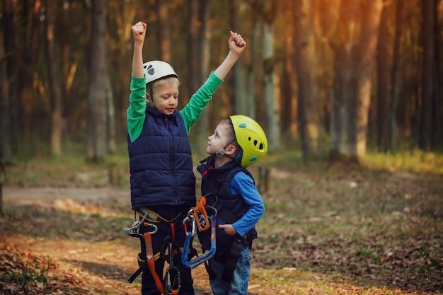 Dois irmãos adoráveis corajosos felizes, retrato duplo, olhando