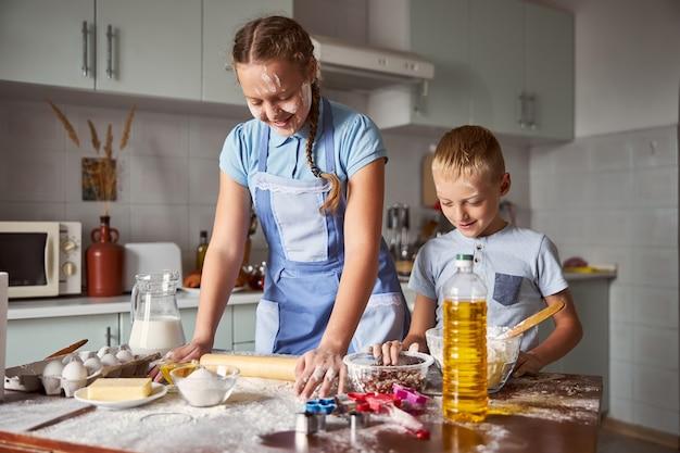 Dois irmãos alegres experimentando massa na cozinha