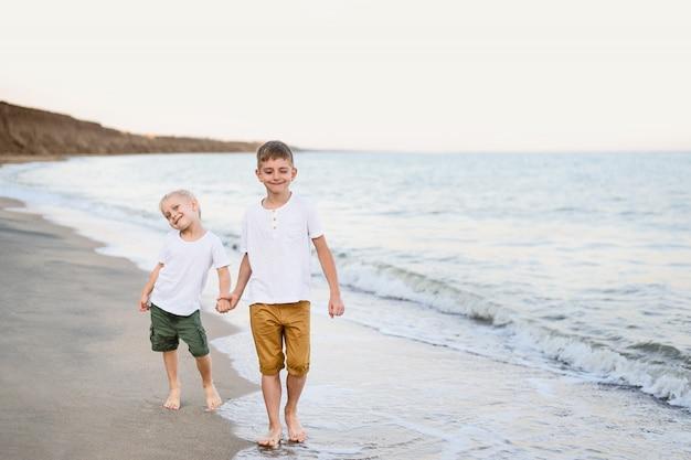Dois irmãos andam pela mão ao longo da costa do mar.