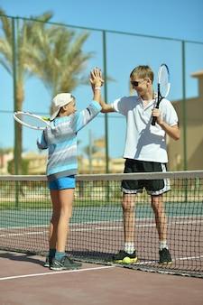 Dois irmãos ativos jogando na quadra de tênis
