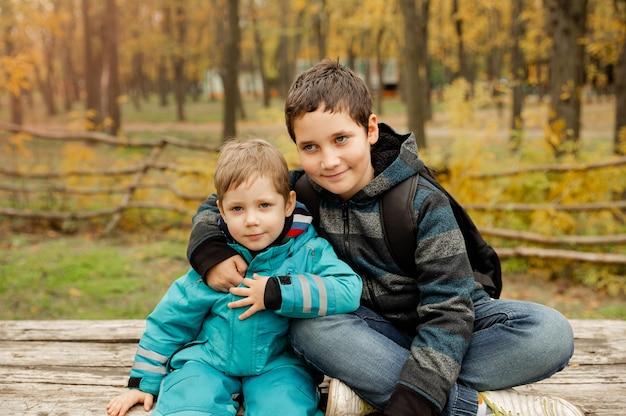 Dois irmãos brincam ao ar livre no outono melhores amigos dois meninos felizes