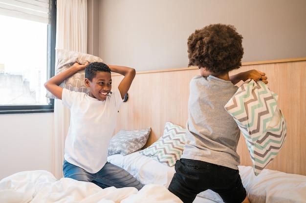 Dois irmãos brincando com almofadas em casa.