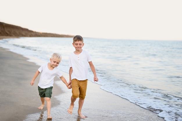 Dois irmãos caminham pela mão ao longo da costa marítima. férias com a família. amizade