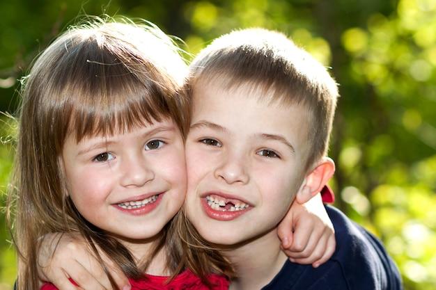 Dois irmãos de sorriso felizes engraçados louros bonitos das crianças, menina nova do irmão do irmão do menino que abraça fora na natureza verde-clara ensolarada do bokeh. relação de família, amizade e conceito de amor.