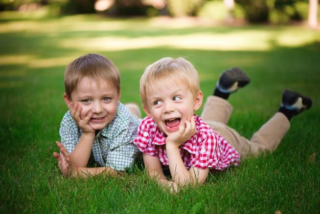 Dois irmãos deitados na grama em um parque ao ar livre, sorrindo e rindo