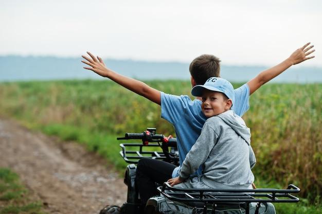 Dois irmãos dirigindo uma quadriciclo atv de quatro rodas. momentos de crianças felizes.