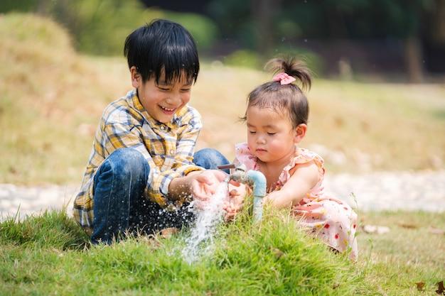 Dois irmãos e irmãs jogam água da torneira