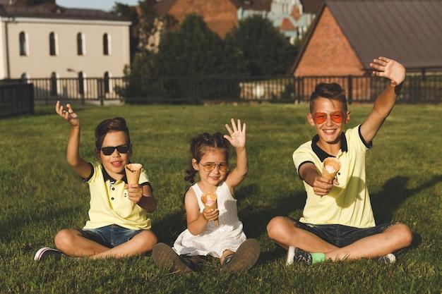 Dois irmãos e uma irmã sentam-se na grama com sorvete.